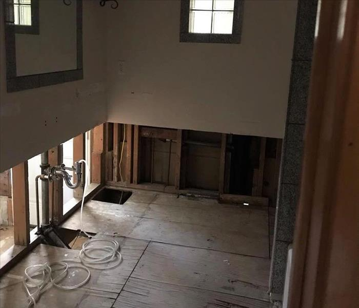 image of bathroom with 3 foot cuts up the drywall and unfinished flooring