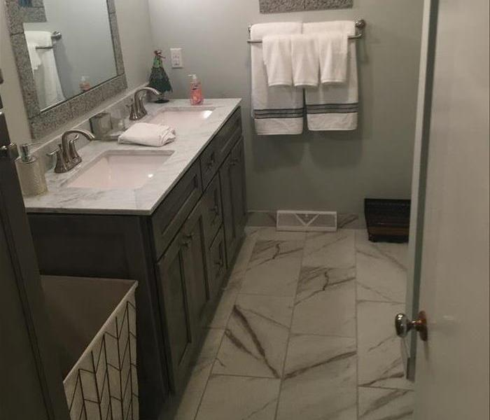 image of same bathroom fully re-done with brand new cabinets and flooring