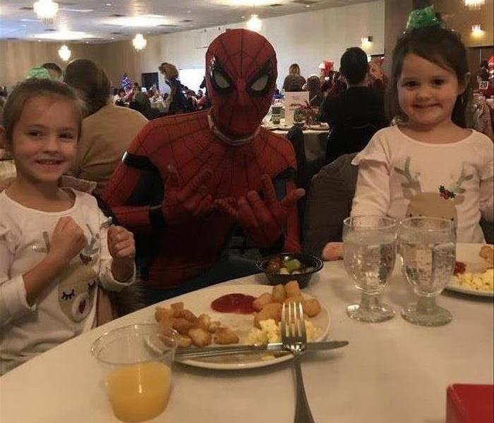 Spiderman character posing with two small children while eating breakfast