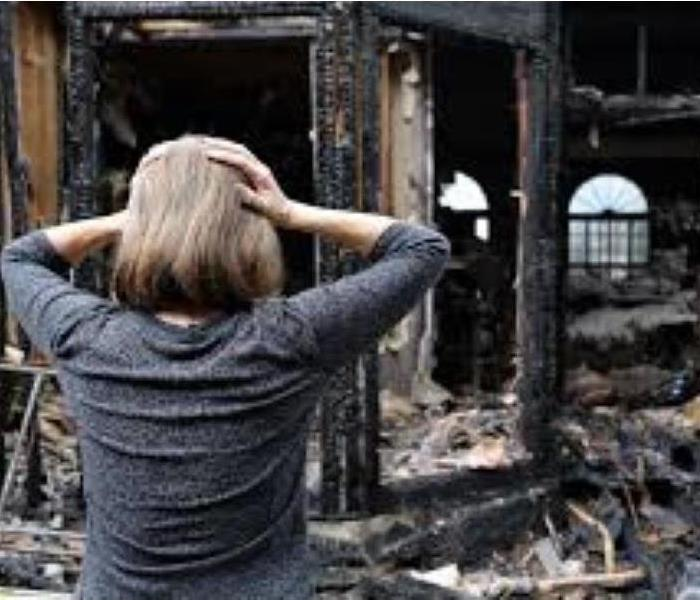 woman holding her head with both hands and observing the damage as a result of a fire to her home